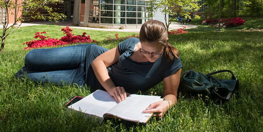 student reading in the grass